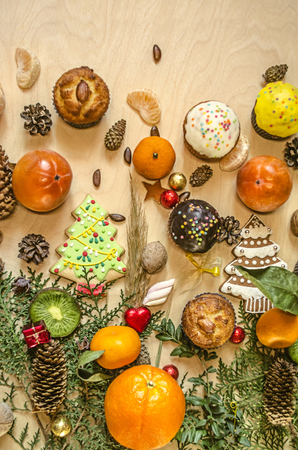 Different citrus,persimmon,biscuits spruce and muffins on a branch of cypress with pine cones,nuts,chocolate balls on plywood