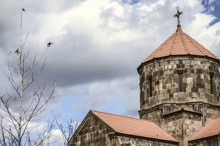 Yerevan; Armenia; the community Nerkin Charbakh; 2 February; 2018: Storm clouds over the dome in the form of an umbrella covered with red tiles with forged cross  in the Church of the Holy Cross in the suburbs of the capital of Armenia