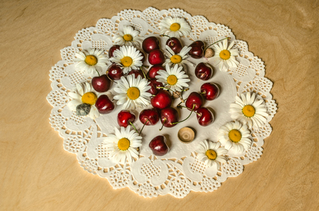 Laced oval white paper napkin  with red cherries and flower heads of daisies on plywood table Banque d'images