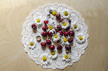 Oval white laced paper napkin  with red cherries and flower heads of daisies on a wooden table Banque d'images