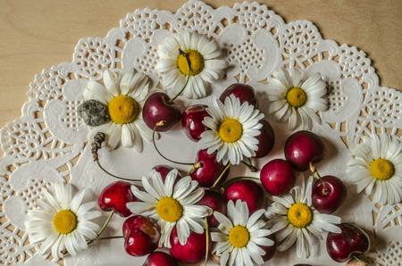 Group with flower heads of field daisies and red cherries on an openwork white paper napkin on a wooden table