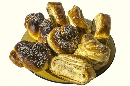White background with sweet rolls covered with sesame seeds with Gata and Eclair on a yellow ceramic plate