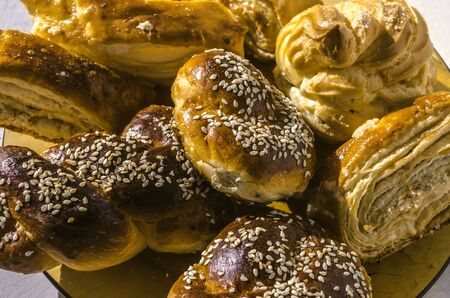 Raisin buns covered with sesame seeds next to eclairs and traditional Armenian pastry Banque d'images
