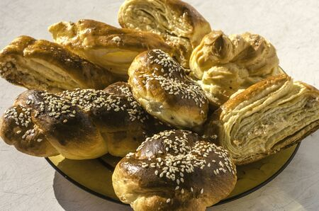 Sweet rolls covered in sesame seeds with Gata and Eclair in a yellow ceramic plate on the old kitchen table