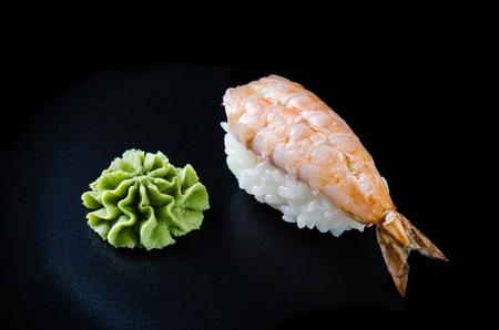 Nigiri sushi made from shrimp, wasabi and japanese rice. Sushi close-up on a black background. Japanese food.