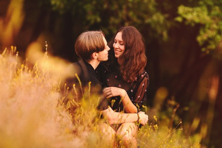 couple hugging in a field at sunset