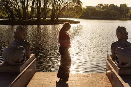 Pregnant girl is standing near pond