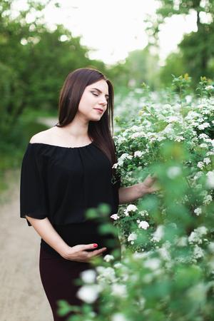 Pregnant girl near spiraea bush Reklamní fotografie