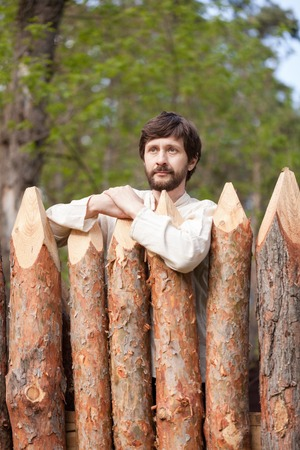 Man with beard in rural shirt stands at wooden fence