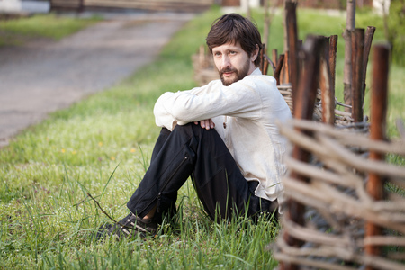 Man with beard in rural shirt sitting on grass