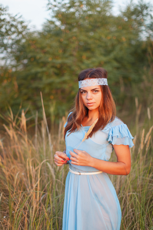 Charming young girl in transparent blue dress is standing in field at sunset