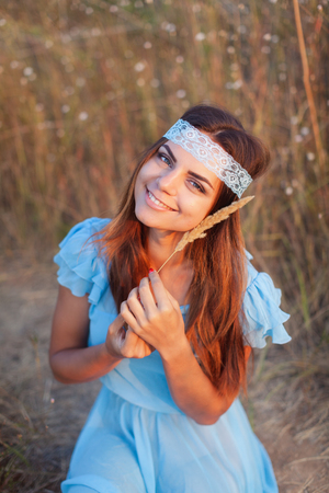 Charming young girl in transparent blue dress is sitting in field at sunset