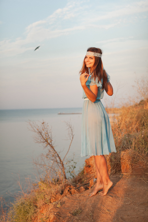 Charming young girl in transparent blue dress is standing near sea at sunset Reklamní fotografie