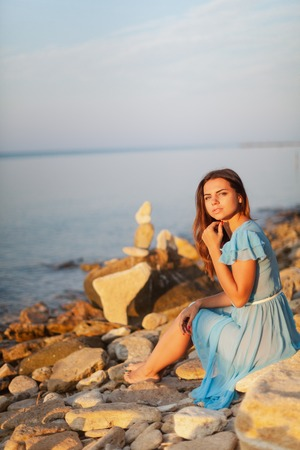 Charming young girl in blue dress is sitting on stones by sea at sunset