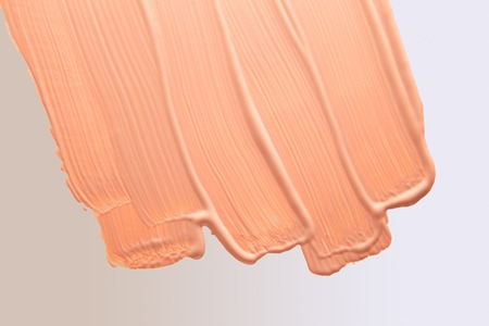 Smudged liquid make-up base on a white gradient background