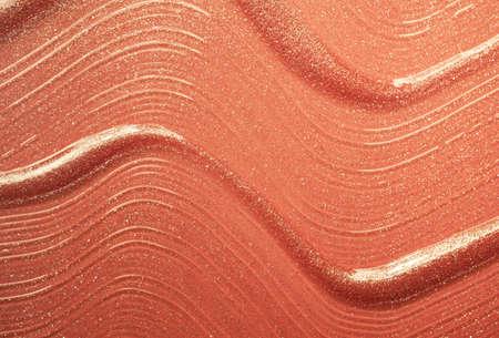 Glossy goldenbrown orange lipstick background texture smudged