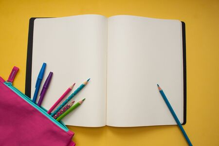 Back to school. Empty notebook and colorful pencils on yellow background