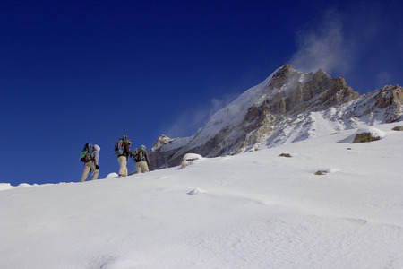 purposefulness: A team of mountaineers going to summit with snow and wind