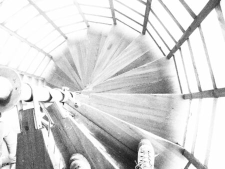 Circular stairs in tower at the top of the Giant mountains, Czech republic with shoes at the begining. Black and white photo.