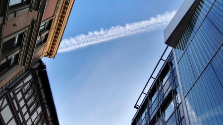 Bue sky among buildings, taken from ground, with white line after airplane flight.
