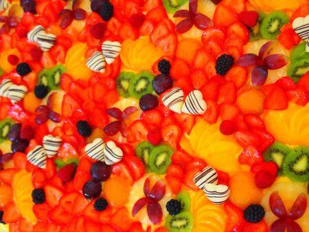 白いボンボンハート、イチゴ、ブラックベリー、キウイ、アプリコットと色彩フルフルフレームウェディングケーキ。 写真素材