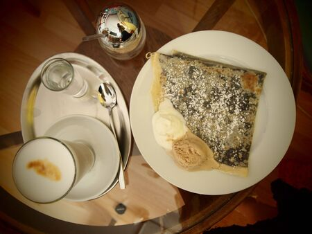 Caffe latte, pancake with chocolate and suggar on table, up sight on table