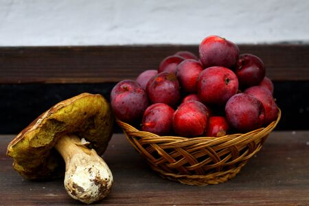 Very big mashroom and red basket with red apples on wood bank, white background.