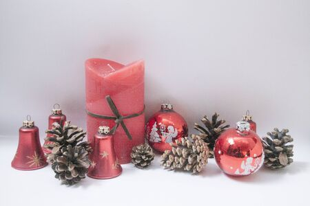 red candle and pine cones and red christmas ornaments on white backround