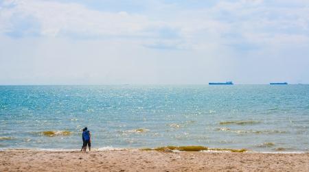lejos: Dos hombre en la playa mirando a los buques de carga en la distancia