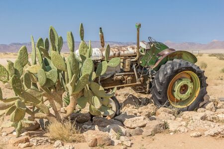 Abandoned rusted tractor with cactus in the foreground in Solitaire, Namibia Stok Fotoğraf