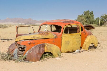 Abandoned yellow orange car in Solitaire with trees in the background in Namibia