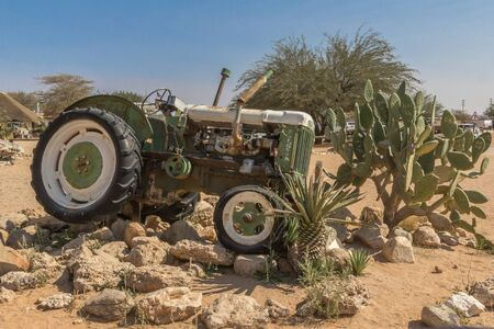 Abandoned rusted tractor over rocks with cactus in the middle of the desert in Namibia