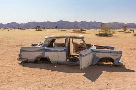 Abandoned car with open doors in the middle of the desert in Solitaire, Namibia