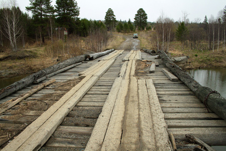 wide wooden bridge of planks over the river and forest road with a car