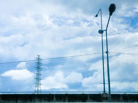 Pylon en hoogspanningstransmissiekabel in bewolkte hemel. Stockfoto
