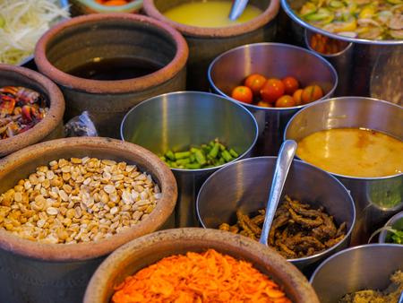 ingredients for Som tam or Som tum (Thai papaya salad), dried shrimp, toasted peanut, tomato, snake beans, shredded green papaya, fish sauce, lime juice.