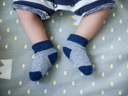 Baby feets in blue socks. keep baby feet warm in winter