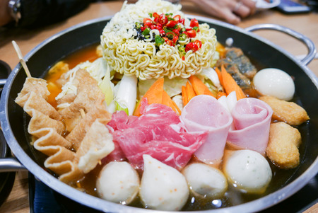 Korean Hot pot Budae Jjigae or Army Stew is Korean fusion food incorporates American style with noodle, ham, sausages, canned baked beans, sliced cheese and Kimchi. Stock Photo
