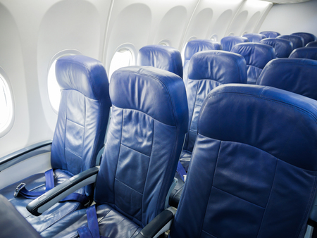 windows: Interior of commercial airplane cabin with blue passenger seats.