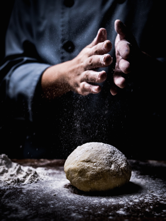 pastry chef hand sprinkling white flour over Raw Dough. Banque d'images