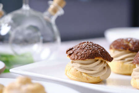 choux cream or cream puff or French profiteroles with fresh cream set on cafe table.