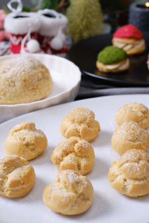 christmas choux cream or cream puff or French profiteroles with fresh cream set on cafe table.