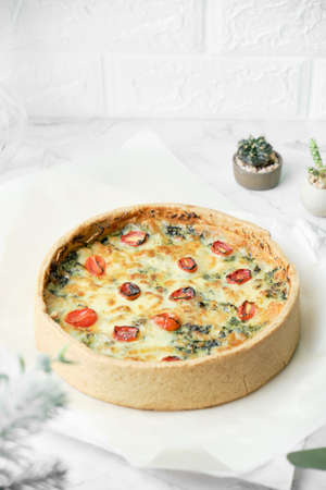 Homemade cheesy spinach quiche for brunch. set on white cafe table background. Zdjęcie Seryjne