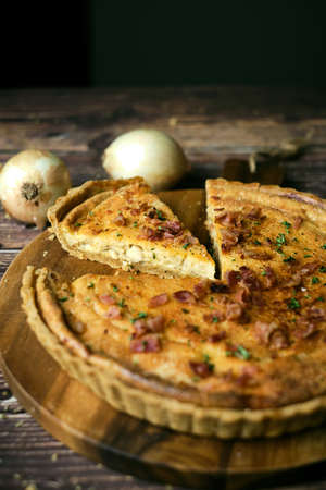 Homemade cheesy quiche lorraine for brunch. set on wooden cafe table background.