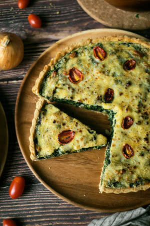 Homemade cheesy spinach quiche for brunch. set on wooden cafe table background.