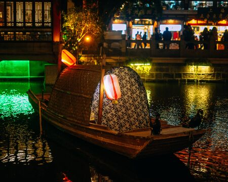 Traditional chinese boat with paper lanterns and lights in a lake at night