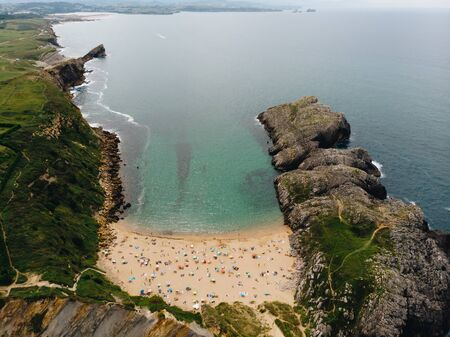 Aerial shot of beautiful spanish beach with turquoise water and rocky cliffs