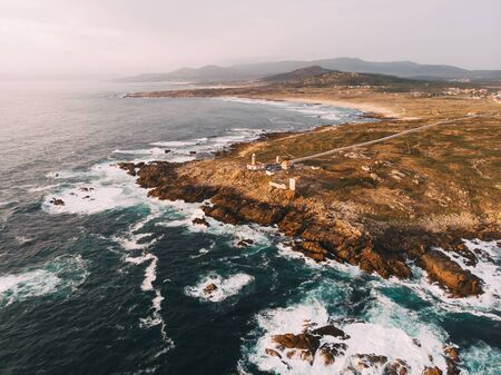 Aerial view of rocky coastline and Lighthouse at sunset in northern spain Archivio Fotografico
