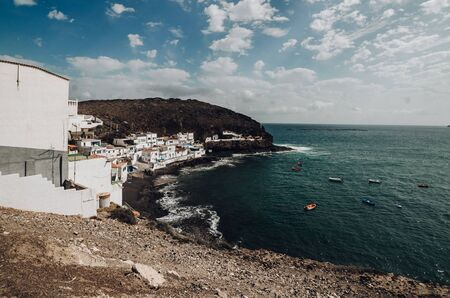 Beautiful village in Canary island with white houses with boats in the atlantic ocean