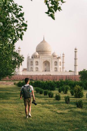 Beautiful shot of Taj Mahal at sunset with young man walking in garden